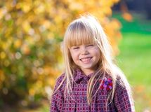 Face, fun, close up. Beautiful little blonde hair girl, has fun smile face, happy brown eyes, white teeth. Child portrait. Creative concept. Autumn time. Close stock photos