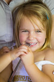 Beautiful little blondie girl playing with fork Stock Photo