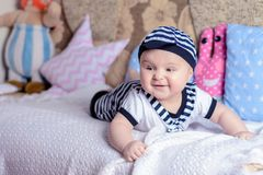 A beautiful little boy in a costume sailor lays on a bed near the pillows stock photo