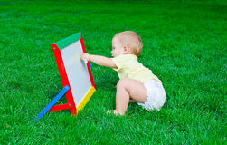 А beautiful little boy draws sitting on a lawn. А beautiful little boy draws a marker on a board sitting on a lawn Royalty Free Stock Image
