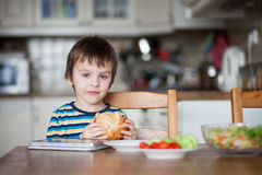 Beautiful little boy, eating sandwich at home Royalty Free Stock Photos