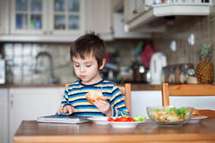 Beautiful little boy, eating sandwich at home Stock Image