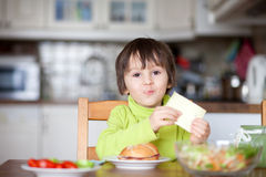 Beautiful little boy, eating sandwich at home Stock Photos