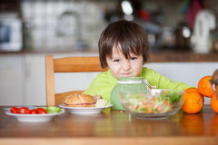 Beautiful little boy, eating sandwich at home Stock Photo