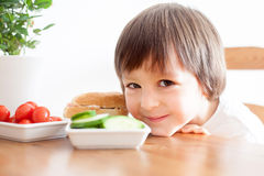 Beautiful little boy, eating sandwich at home, vegetables on the Stock Images