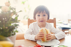 Beautiful little boy, eating sandwich at home, vegetables on the Stock Image