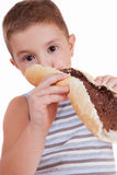 Beautiful little boy eats bread with chocolate cre Royalty Free Stock Photo