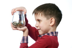 Beautiful little boy with glass jar of coins isolated Royalty Free Stock Photos