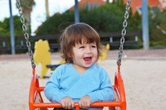 The beautiful little boy laughs  at a red swing Stock Image