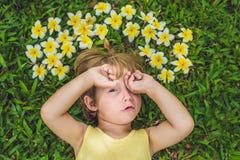 Beautiful little boy lies on meadow with frangipani royalty free stock image