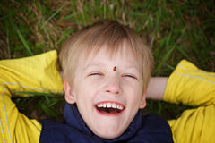 Beautiful little boy lies on meadow and smiling with ladybug on Stock Photo