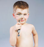 Beautiful little boy looking through a magnifying glass Stock Images