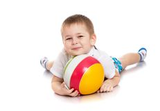 Beautiful little boy lying on the floor hugging. Striped ball - isolated on white background Royalty Free Stock Image