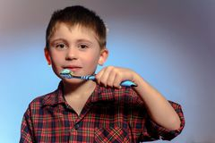 A beautiful little boy in a pajamas smiles and holds in his hand a toothbrush on a blue background stock photos