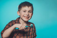 A beautiful little boy in a pajamas smiles and holds in his hand a toothbrush on a blue background stock images