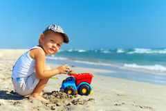Beautiful little boy playing on the beach Stock Image