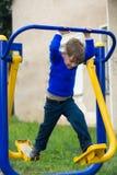 A wonderful Ukrainian boy performs exercises on simulators royalty free stock image