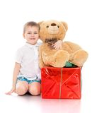 Beautiful little boy sitting on the floor. Next to the gift, a large Teddy bear and gift opakowanie in the big red box - isolated on white background Royalty Free Stock Image