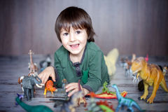 Beautiful little boy, smiling at camera, animals and dinosaurs a Stock Image