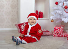 Beautiful little boy in a suit of Santa Claus under the Christma Stock Images
