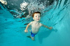 Beautiful little boy swimming underwater in pool on blue background. Portrait. Shooting under water at the bottom. Horizontal view Stock Photography