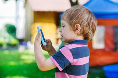 Beautiful little boy taking picture with mobile in summer garden Royalty Free Stock Photos