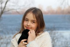 Beautiful little brown-eyed girl looking at camera hugging her soft toy. Close-up, outdoors stock photography