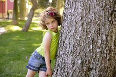 Beautiful little brunette girl beside a tree trunk Royalty Free Stock Photos