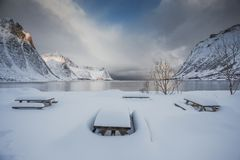 Beautiful little campsite with amazing views of the sea and mountains. Benches and a table covered with a thick layer of snow on the Lofoten Islands in Norway royalty free stock images