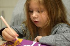 A beautiful little caucasian white girl child with long blond curly hair and concentrating expression in the pretty face painting royalty free stock photography