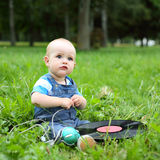 Beautiful little cheerful boy with record and headphones in summer park Stock Photography