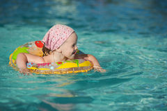 Beautiful Little cheerful girl swimming in the pool Stock Photos