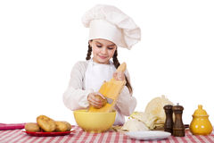Beautiful little chief cooker on the desk with vegetables Royalty Free Stock Image