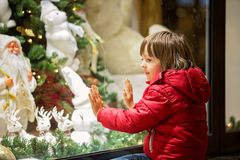 Beautiful little child, boy, watching Christmas decoration with toys in a shop window display, wishing for a present. His reflection in the window royalty free stock photos