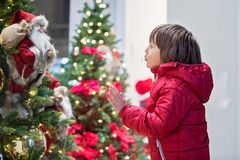 Beautiful little child, boy, watching Christmas decoration with toys in a shop window display, wishing for a present. His reflection in the window stock photos