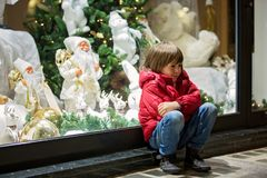 Beautiful little child, boy, watching Christmas decoration with toys in a shop window display, wishing for a present. His reflection in the window stock photo