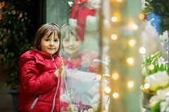 Beautiful little child, boy, watching Christmas decoration with toys in a shop window display, wishing for a present. His reflection in the window stock image