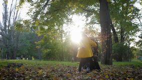 Beautiful little child girl with her loving mom plays with fallen leaves in autumn park during family walk, fall season