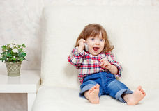 Beautiful little child holds a cell phone. Foto-beautiful little child holds a cell phone royalty free stock photos