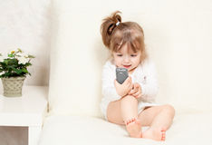 Beautiful little child holds a cell phone Royalty Free Stock Photos