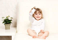 Beautiful little child holds a cell phone Stock Images