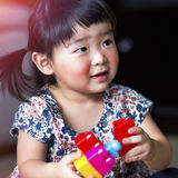 Beautiful little child playing colorful toy joyfully Royalty Free Stock Photography