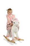 Beautiful little child riding her toy horse Royalty Free Stock Photography