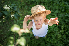 Beautiful little child with straw hat looking up and hand waving Royalty Free Stock Photos