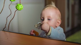 Beautiful little child stretch to pick up the pacifier. Slow motion close-up high quality shoot of a cute little baby boy stretch hi little arms towards the stock video footage