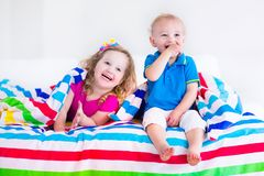 Beautiful little children sleeping under colorful blanket. Two kids sleeping in bed under colorful blanket. Children relaxing in bedroom. Tired toddler girl and Stock Photo