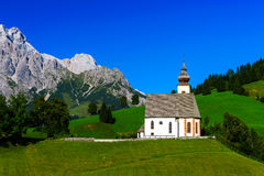 Beautiful little church in Alps. Sunny day, green grass on the h Stock Photo