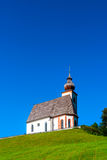 Beautiful little church in Alps. Sunny day, green grass on the h Royalty Free Stock Images