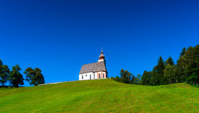 Beautiful little church in Alps. Sunny day, green grass on the h Royalty Free Stock Photos