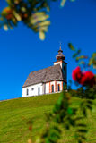 Beautiful little church in Alps. Sunny day, green grass on the h Stock Photography